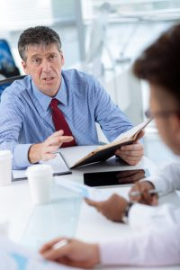 Angry mature businessman talking to his employees